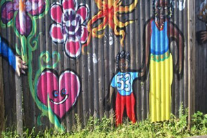 Fence artwork depicting family, hearts and flowers in beautiful hues.