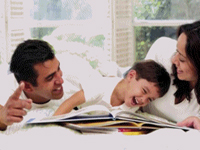 Mother and Father and son - laughing and enjoying reading.