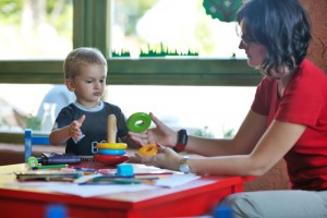 Child learning with an adult: 'r kids Family Center offers a number of educational services to support children and their families.